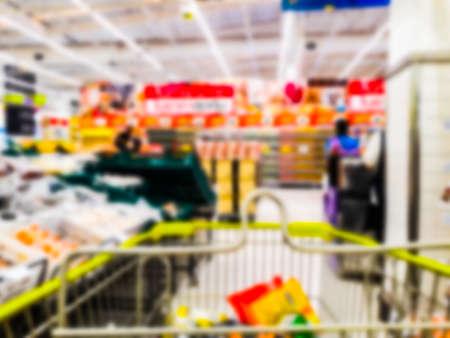 Abstract blurred supermarket aisle with colorful shelves and unrecognizable customers as background Banco de Imagens - 131443338