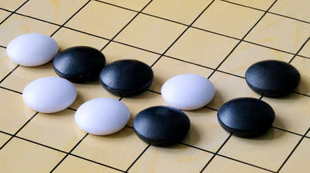 Chinese go game board, close up view of playing black and white stone pieces - Image
