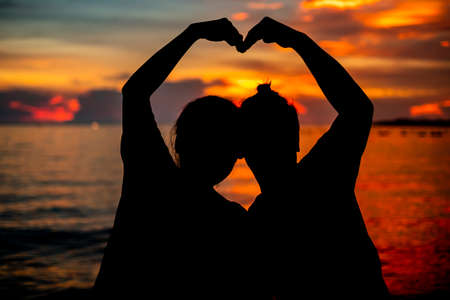 Two lovers (girl and boyfriend) hold hands at the sunset sunsets on the beach of the ocean. Love, romance, family, caring. Banco de Imagens - 131442957