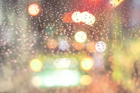 Blurred background. Night city lights blur. Road view through car window with rain drops