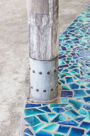 Wooden stakes and mosaic floor from ceramic broken tile