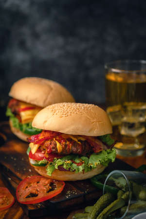 Delicious home made hamburger with beef, ketchup, mustard and fresh vegetables served on wooden board. Free space for text