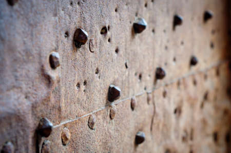 detail of old rusty metal sheated door with rivets photo