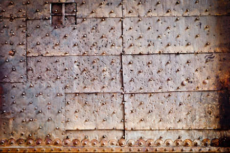rivets and ornament on old rusty metal door Stock Photo