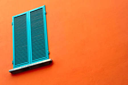 window on orange wall with closed blinds photo
