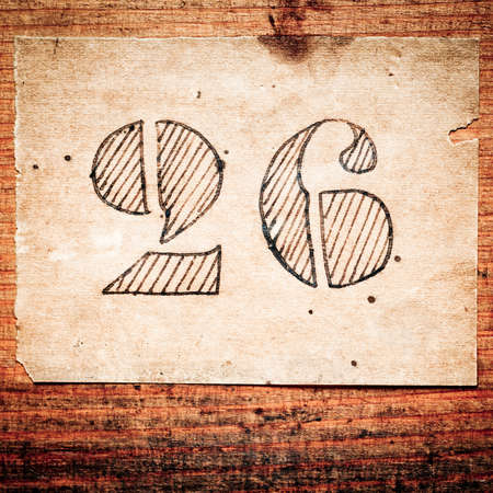 old paper with hand drawn number 26 on wood background Stock Photo - 13171646