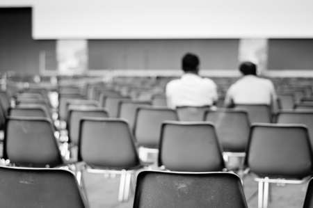 two men sitting in row of empty chairs waiting for the show