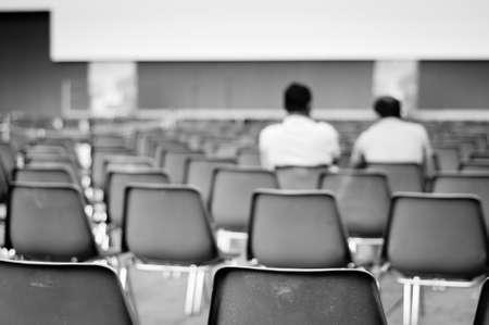 Zwei Männer sitzen in der Reihe der leeren Stühle warten auf der Messe Lizenzfreie Bilder