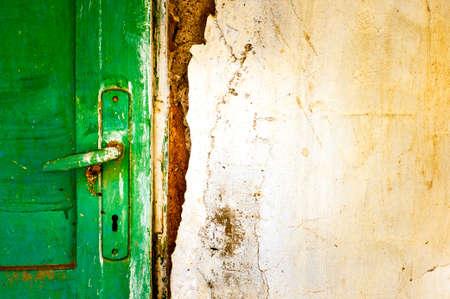old door handle detail. wooden door on damaged wall close-up photo