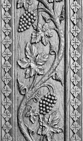 wood craft: Wood carved ornament background. Grapes decoration craving on black wood. Old traditional ornament.