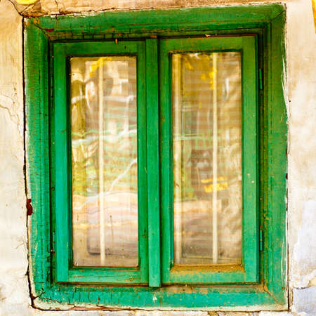window of old house. wooden window frame green painted. dirty destroyed house detail. photo