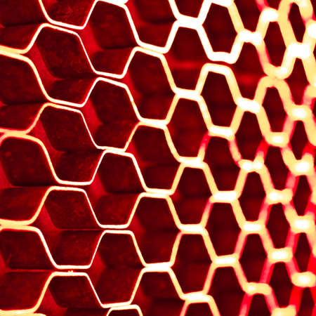 dof: Abstract hexagonal structure with shallow dof. Red metal honeycomb mesh. Technology concept.