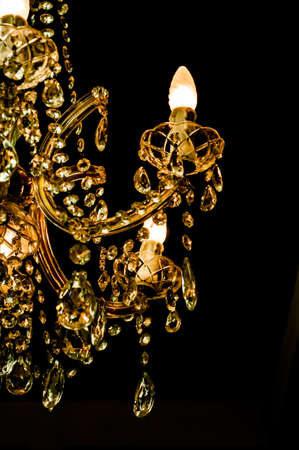amber light: Beautiful crystal chandelier isolated on black background. Amber light.