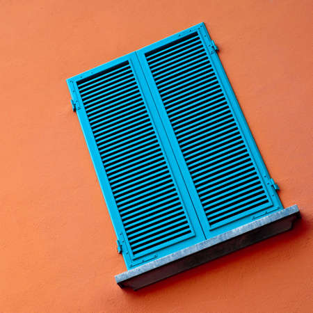 venetian blind: window on orange wall with closed blue blinds