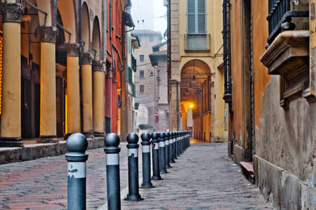 Old street view Bologna city, Italy. Cobble stone street with bollards. Renaissance buildings.