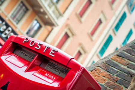 Red letter box. Italian mail service box. Traveling. City street view Italy.
