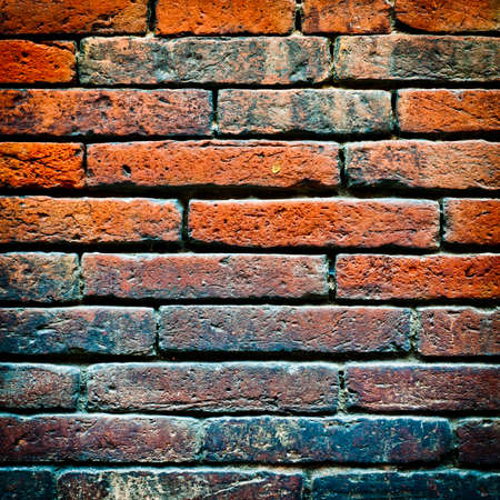 Brick wall texture background. Weathered brown stone facade. photo