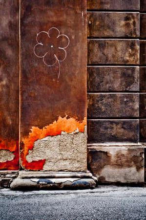 italian architecture: Flower graffiti on an old damaged wall. Italian architecture detail.