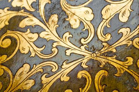 carvings: Fourish pattern. Gold leaf floral design on black background. Old, antique surface.