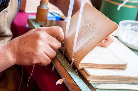 Buchbindung Prozess. Männliche Arbeitnehmer verbindliche Seiten. Reparieren eines alten Buch. Buchbinderei sweing Buchrücken.