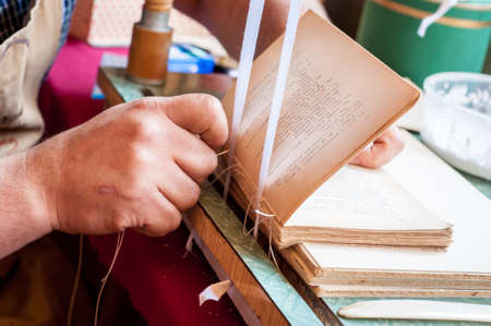 Book binding process. Male worker binding pages. Repairing an old book. Bookbinder sweing book spine. Banque d'images