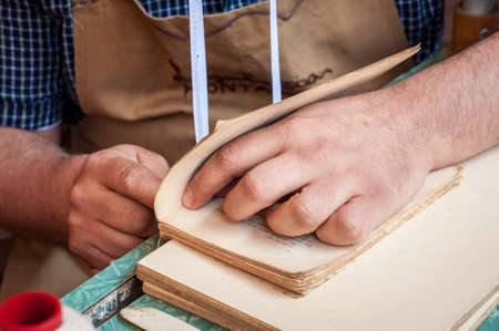 book binding: Book binding process. Male worker binding pages. Repairing an old book. Bookbinder sweing book spine. Stock Photo