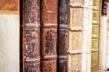 Row of old leather covered books. Aged, used books.