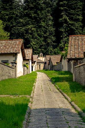 Stone houses and walls in monastery courtyard. Stone path to chapel. Camaldoli monastery, Italy. Stock Photo