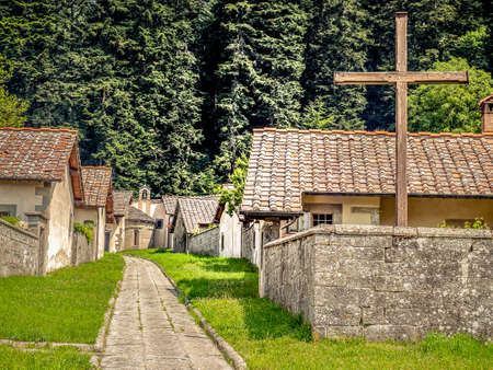 Cross in monastery settlement. Stone houses and walls in monastery courtyard. Christian cross. Camaldoli monastery, Italy. Stock Photo