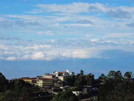 visible: Clouds rolling on the small hill villages (visible among the green hills) of Kodaikanal in India. Stock Photo
