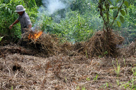 A resident light fires to clear land in Sambas district, West Kalimantan province.