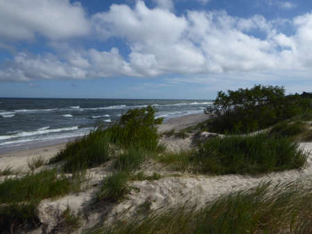 Sand dunes with grass at baltic sea beach with waves and clouds in Poland Stock Photo