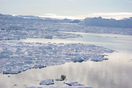 Small boat in disco bay, Greenland sailing through pack ice