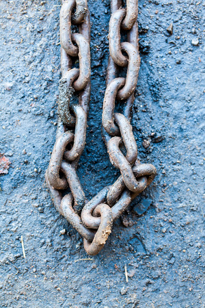 chain links: Old chain links on oil contaminated ground in light nature