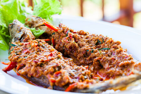 sheat fish: Close-up fried whisker sheat fish with chili sauce, or chili sauce on fried fish on white dish, Thai food Stock Photo