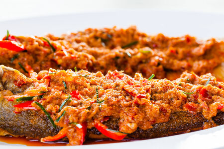 Close-up fried whisker sheat fish with chili sauce, or chili sauce on fried fish on white dish, Thai food Stock Photo
