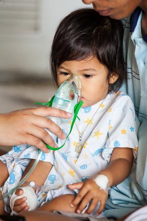 아기의 얼굴에 의료 마스크 씌우기 스톡 콘텐츠
