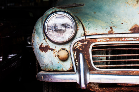 Detail of the front headlight of an old car in garage Foto de archivo