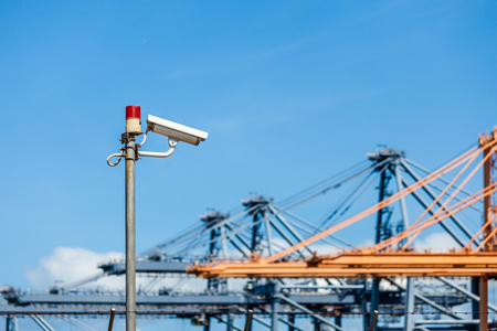 warning lights: CCTV cameras with warning lights on steel pole and blurred crane in port background Stock Photo