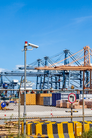 warning lights: CCTV cameras with warning lights on steel pole and crane in trade port background