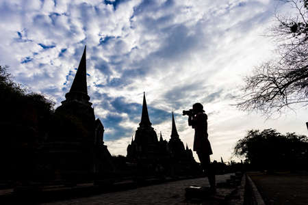 historic sites: Silhouette of Traveler take a picture of Ayutthaya Old Town filled with historic sites, Ayutthaya Historical Park, Thailand