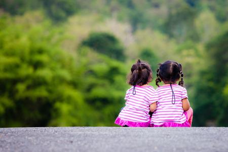 mignonne petite fille: Vue arrière de deux petite fille assise sur le sol au parc