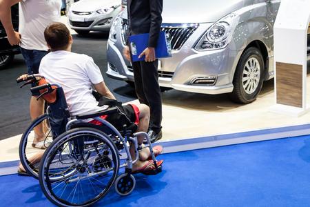 paraplegic: Hombre en silla de ruedas con el vendedor en el motor de sala de exposición