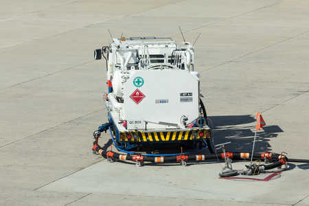 underwing: rear view of service and refuelling truck for the aircraft on airport