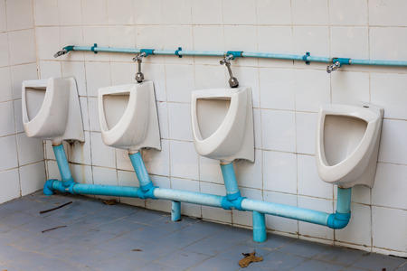 white dilapidated urinal on white wall