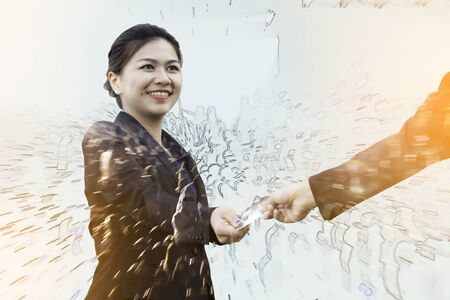 Double exposure of businesswoman exchanging credit card with motion crowd Stock Photo