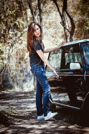 Happy asian youth teenage listening music on cellphone with open the door retro car. Stock Photo