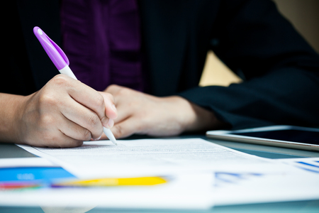 Close-up businessperson signing agreement contract with graph data document on desk Stock Photo