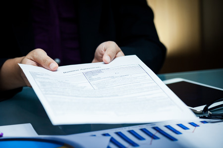 Close-up of businessperson give agreement document with graph data document on desk