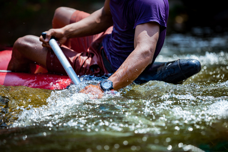 Close-up hand of young men is rafting on the river, extreme and fun sport at tourist attraction